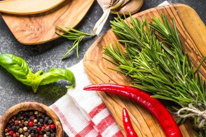 Przyprawy, zioła i naczynia kuchenne na czarnym kamiennym stole. Widok z góry.